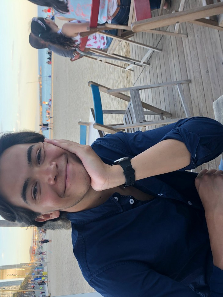 Justin Duyao sitting at a small wooden table on a beach in the late afternoon. Justin has brown hair, and has his elbow propped on the table with his head resting in his hand. He smiles at the camera.