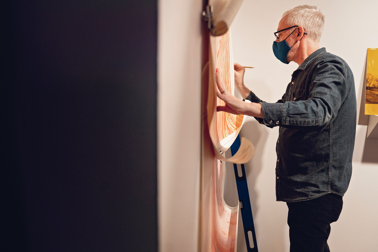 Color photo of a side profile view of Steve Rowell installing his exhibition Uncanny Sensing, Remote Valleys opening at the JSMA . He is holding two maps against a white wall with his left hand. In his right hand he is holding a pencil. He is looking towards at the maps. He is standing up wearing black pants, denim shirt, a mask, and he is wearing glasses. Behind him is a blue ladder.