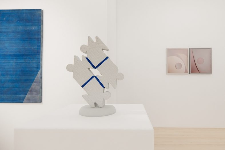 Four pieces displayed in a gallery space, including a single painting hanging on a white wall on the left; a sculpture displayed on a white stand, center frame; and two paintings hanging to the right of the sculpture in the background, also on a white wall. The piece on the left is a large blue painting with textured, horizontal stripes on canvas with a stripe of grey populating the bottom right corner. The sculpture in the middle is a white cement figure resembling a puzzle piece, with both jagged and rounded edges, a hole in the middle and four blue stripes going out from it. The paintings on the right are the same size and close together. One displays a large cream circle, partly out of frame, a pink circle within it and a shadow of the cream circle on a pink background. The other has a pink circle near the center, the same size as the other, with a dark stripe to the left of it, all against a background of the same color pink.