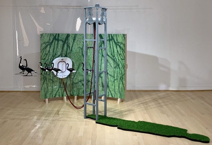 a mixed media work, primarily using turf, first as a tri-panel backdrop for part of the piece, over which what seem to be shadows from tree branches are cast, and secondly as the shadow—in the form of a human's silhouette—of the central object, which seems to be a chair with very tall legs. Behind this, black and white geese walk in a line.