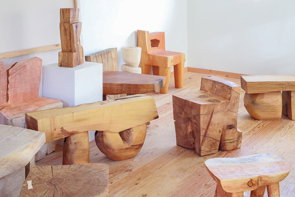 Numerous carved wooden sculptures displayed in a room with wooden floors and white walls, some seeming to be functional (e.g. a chair, a bench) and others seeming to take on abstract forms, including one vertical, rectangular piece displayed on a stand with jagged, irregularly spaced edges cut into it. Most of the pieces have flat faces and 90 degree edges and seem to be cut from similar wood.