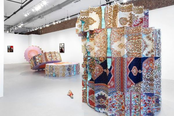 Photo of a gallery space with multiple large sculpture pieces taking up the center of the room, each composed of ornate, multi-patterned fabrics fixed onto a frame or skeleton in large wheel-shaped sections, which are stacked on top of each other. In the rear, two framed pieces hang on the wall.