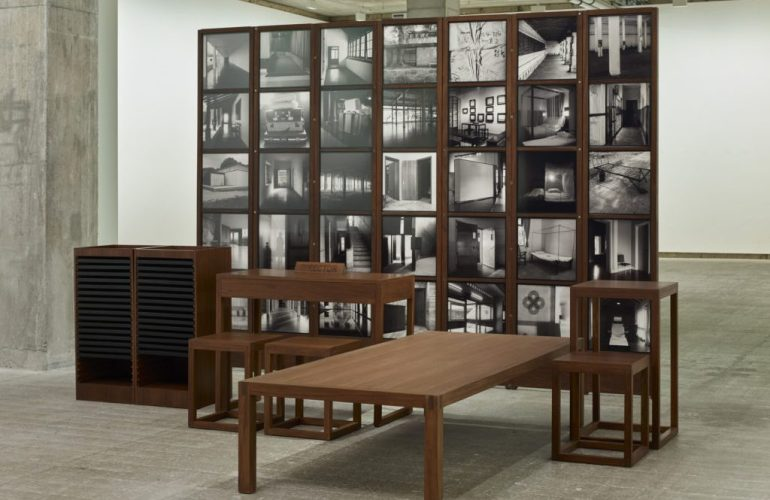 """Photograph of a grid wall of black and white square prints, before which are arranged desks, chairs, and a long table. A sign with the word """"Director"""" rests on one of the desks."""