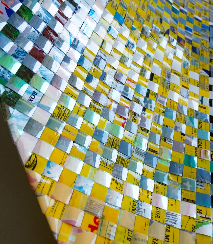 A close up photograph of a multi colored woven object. Equally sized strips of shiny, colorful plastic create a grid of squares that glisten in the light. Each strip appears to be from plastic packaging materials, with colors ranging from yellow to blue and turquoise.