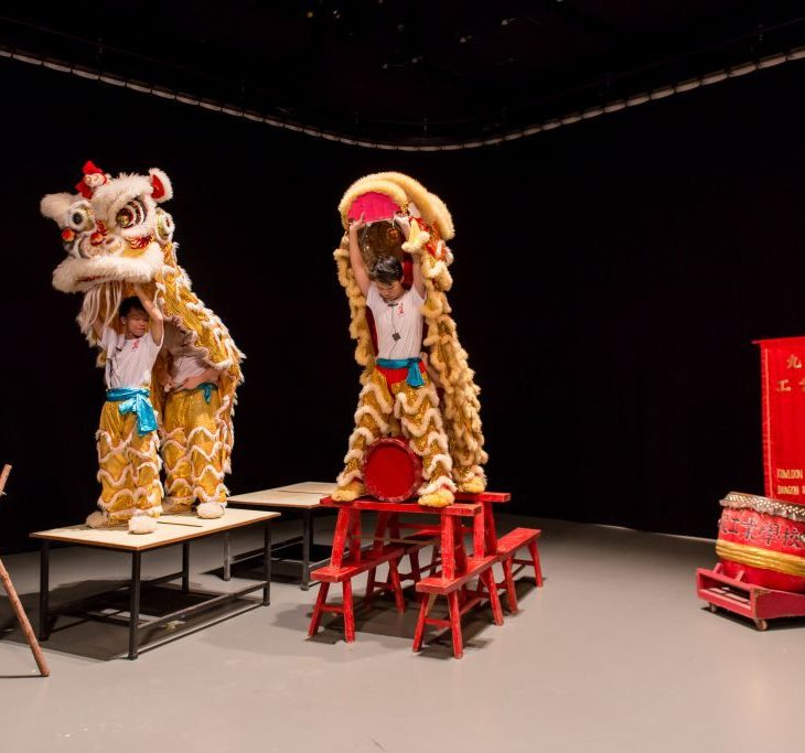 Three men hold the heads of Chinese dragons over their heads. Two of them stand on a table and tuck their white shirts into the legs and feet of the dragon. Another stands atop a pile of six red benches. Behind them is a black curtain; and beside them is a red drum and a banner, on which are printed numerous chinese characters.