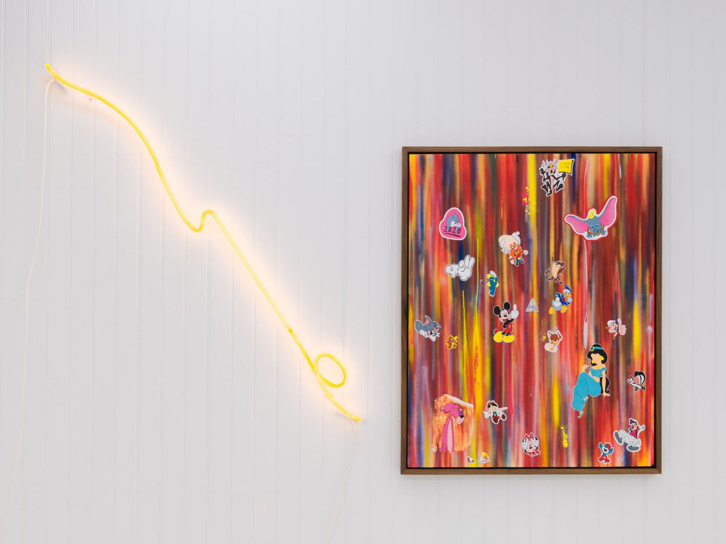 A framed work hangs on a white, paneled wall. On it, what could be stickers of Disney characters—Mickey, Dumbo, and Jasmine—seem to hover against a background of crowded neon brushstrokes (yellows, reds, blues, oranges). A lightning bolt yellow neon tube light hangs beside the work, directing the eye toward it.