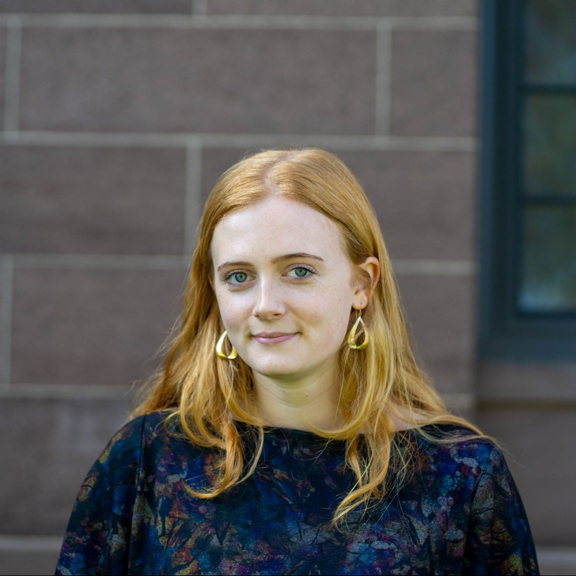 Emma Frohardt standing in front of a brick building. She is a white woman in her twenties with medium-length reddish blond hair. She is wearing gold earrings as she smiles at the camera.