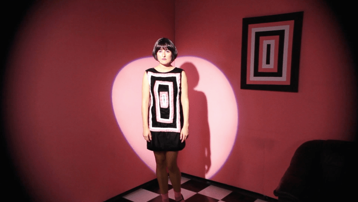 A woman wearing a black dress with rectangles stitched into it stands before a pink wall with a stagelight focused on her, casting a long black shadow behind her. The same pattern on her dress is framed and hung on the wall behind her.