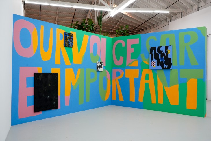 """On two massive panels, their inside edges angled further from the camera than the outside edges, the words """"our voices are important"""" are painted in large, bold lettering, across and through which shapes of orange and pink and green and blue flow. Four canvases with similar art float atop the panels."""