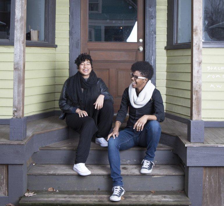 Maya Vivas and Leila Haile sitting on a worn stoop, both laughing.