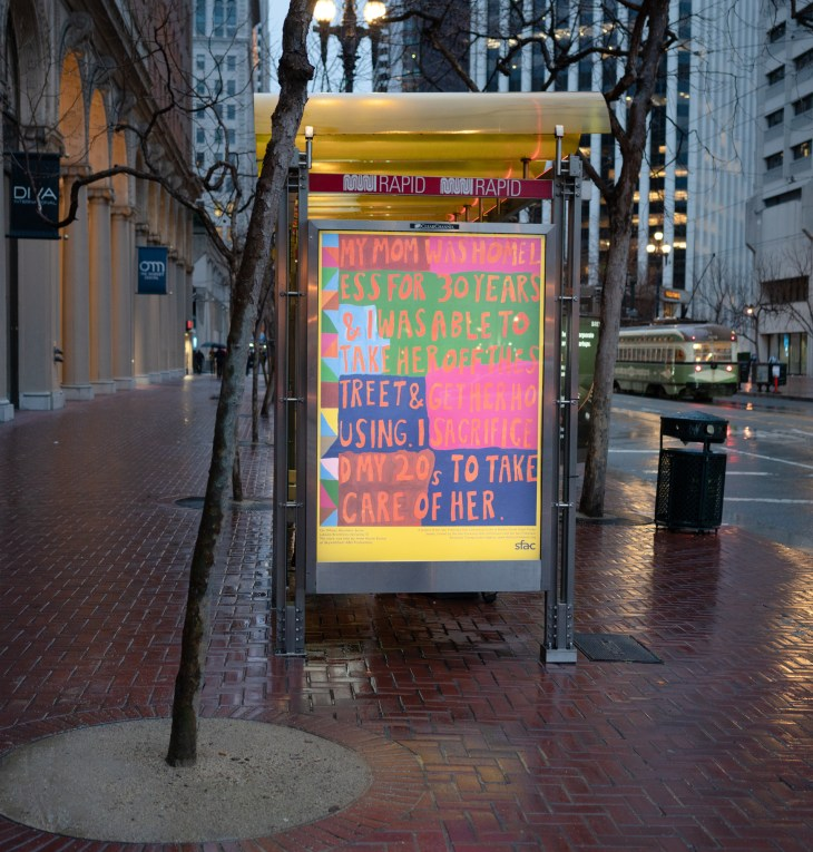 """On a colorful poster installed on a bus stop kiosk in a downtown urban area reads """"my mom was homeless for 30 years & I was able to take her off the street & get her housing. I sacrificed my 20s to take care of her"""" in bolded lettering, against a blocky mosaic of green, navy, pink, red, and various other warm colors."""