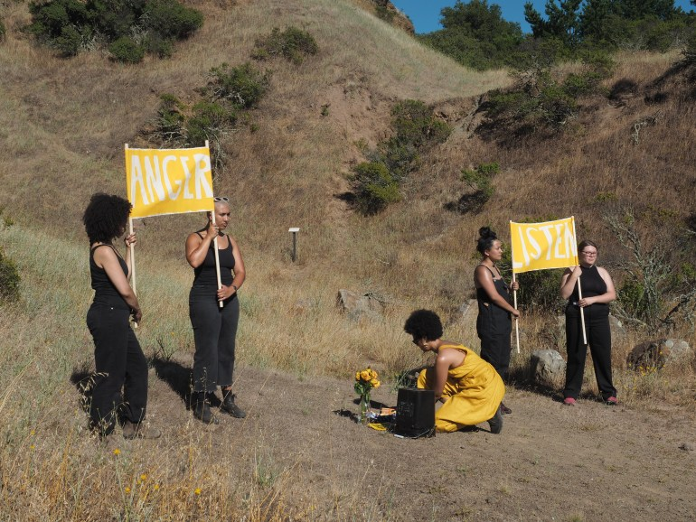 """Photograph of four women wearing all black hold bright yellow banners reading """"ANGER"""" and """"LISTEN"""" stand in a grassy, wilderness area. A woman wearing yellow kneels between them, before her a vase of yellow flowers."""
