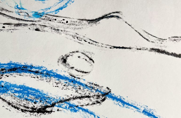 In an intimate photo of a work on white paper, streaks of black and blue race across the page in feverish movement,.