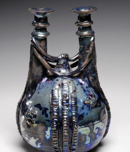 A spherical, squatty bottle with two ornate necks, is draped with braids and shimmers in a semi-rusted, semi-iridescent blue.