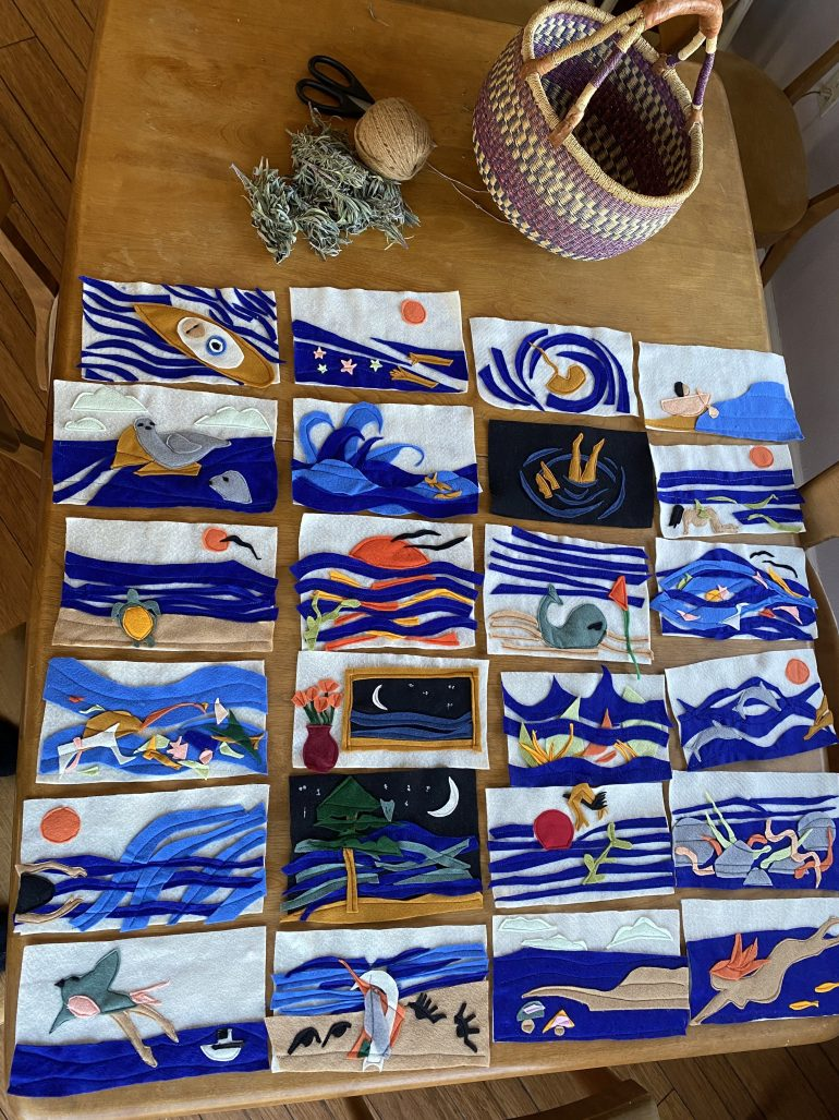 A photograph of sixteen rectangular images made in felt. All the images feature the ocean or water in some way, but each one has a different scene. They're arranged in a grid on a wooden table.