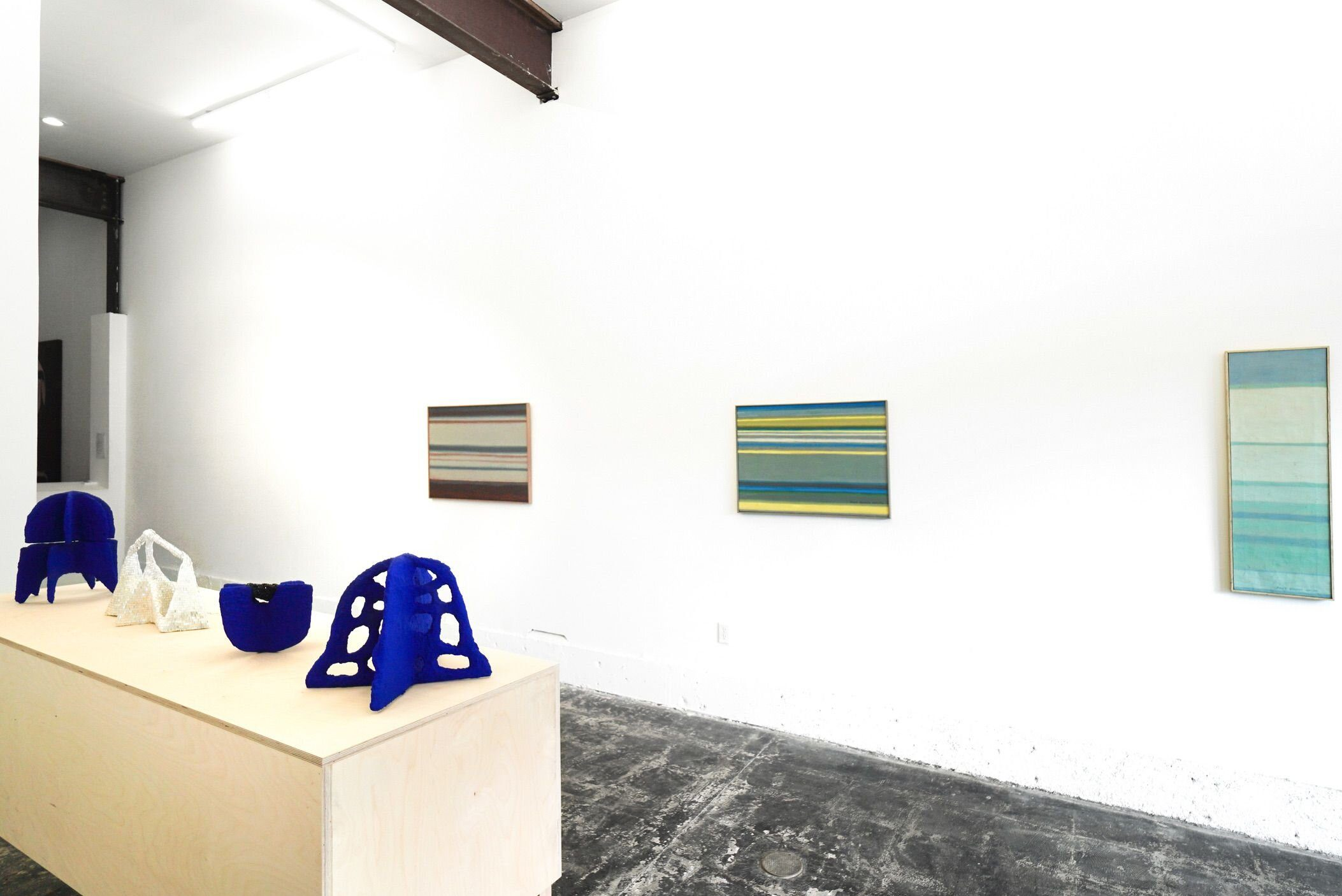 Installation view, with three paintings hanging on a white wall, each of them featuring horizontal lines of varying colors that stack atop each other as in a rainbow or a sunset; then four sculptures sitting atop a table before the paintings—each bold shapes of blue and one of white.