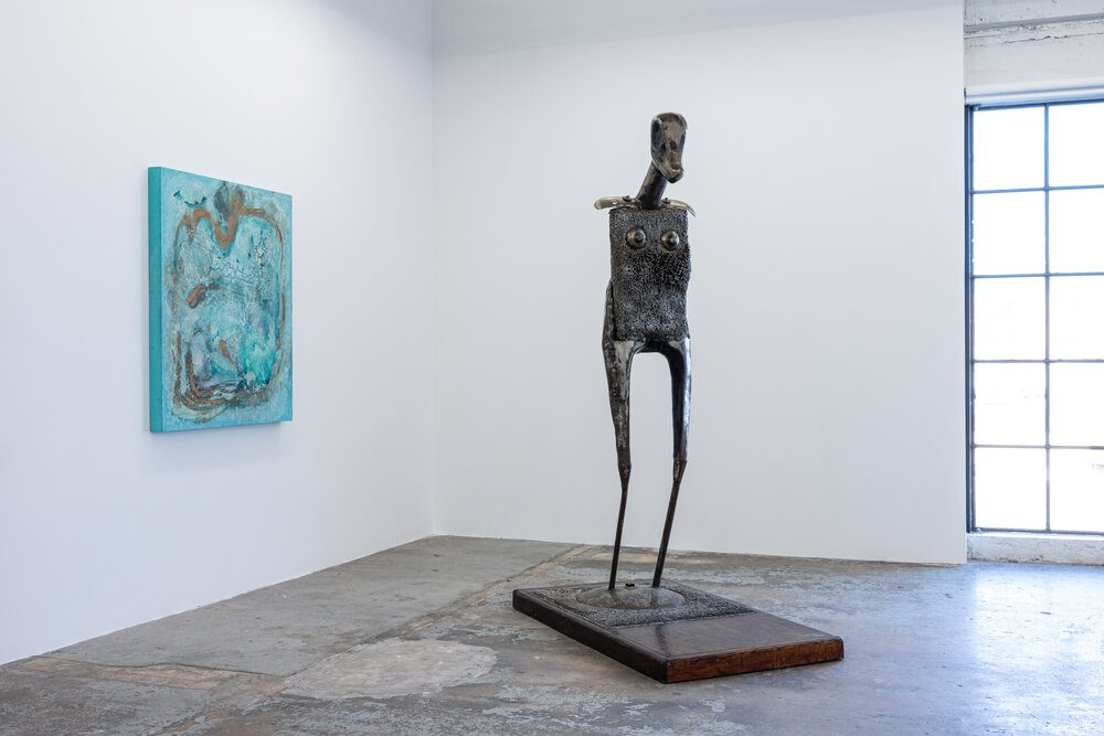 An armless figure with progressively thin legs, a boxy torso, and a long snout stands hesitantly on a block. On a white wall behind it hands a swirling blue painting. Natural light shines in from a window nearby.