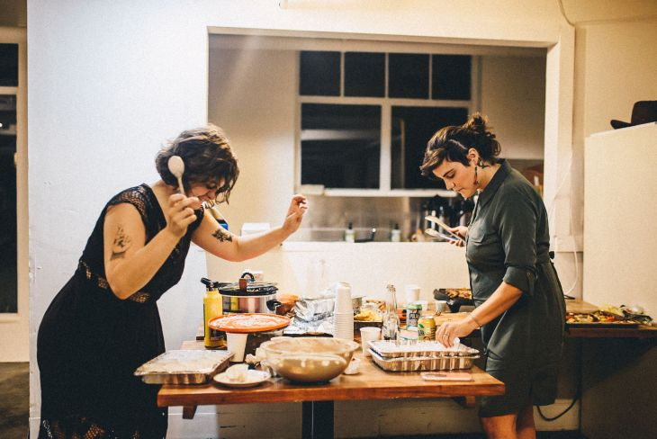 Two women lean over a table of food in a kitchen holding utensils. One dances, while the other reaches for something in a baking sheet.