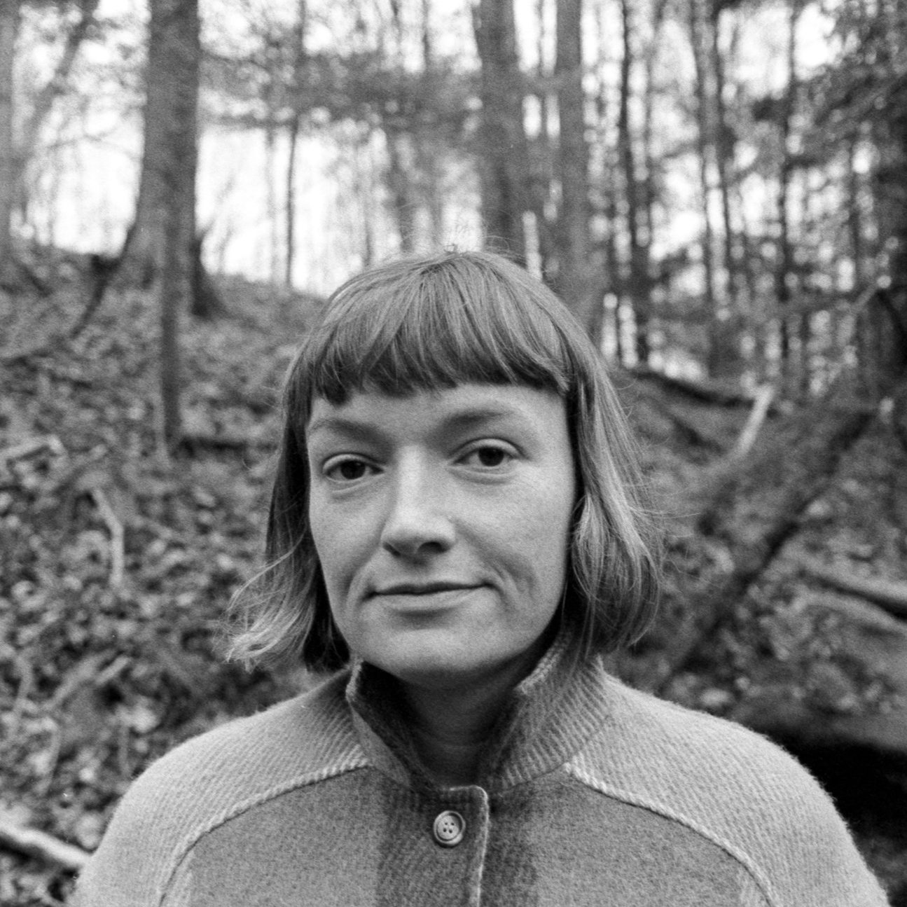 Emma Banks standing in a forest. She is a light-skinned woman with a fringe and wearing a buttoned wool coat.