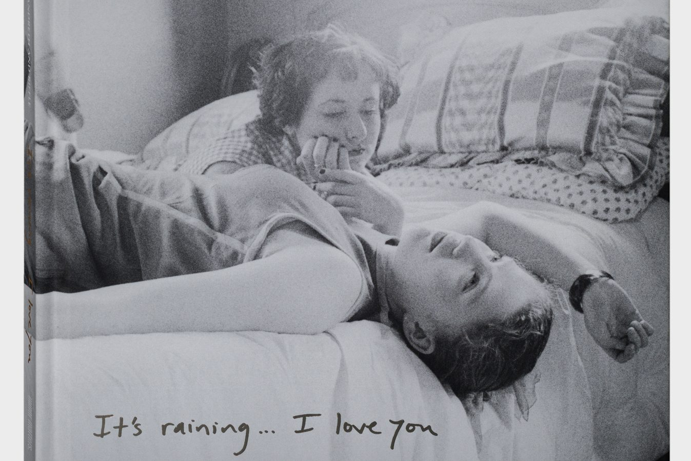"""Photo of the cover of a book, on which two women are lying on a bed—one gazing into space, the other gazing at the one. The title """"It's raining ... I love you"""" is written below."""