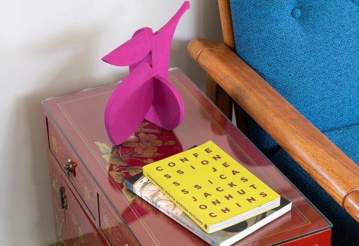 """Beside a blue chair, a small table holds two books, stacked atop each other—the title of the book on top is """"Confessions Jessica Jackson Hutchins""""—and a small pink sculpture, which bulges and reaches and points, with limbs of two dimensional shape and curve."""