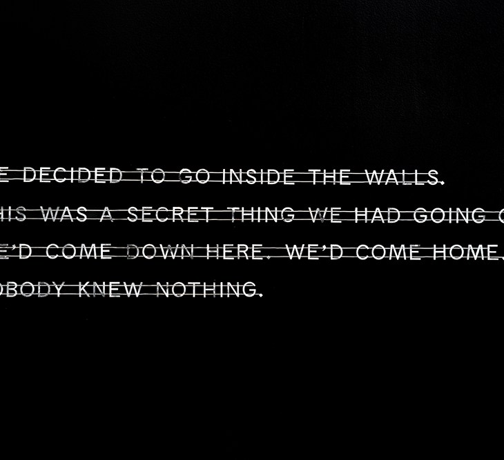 """Silver text fixed onto a jet black background reads """"We decided to go inside the walls. This was a secret thing we had going on. W'ed come down here. We'd come home. Nobody knew nothing."""""""