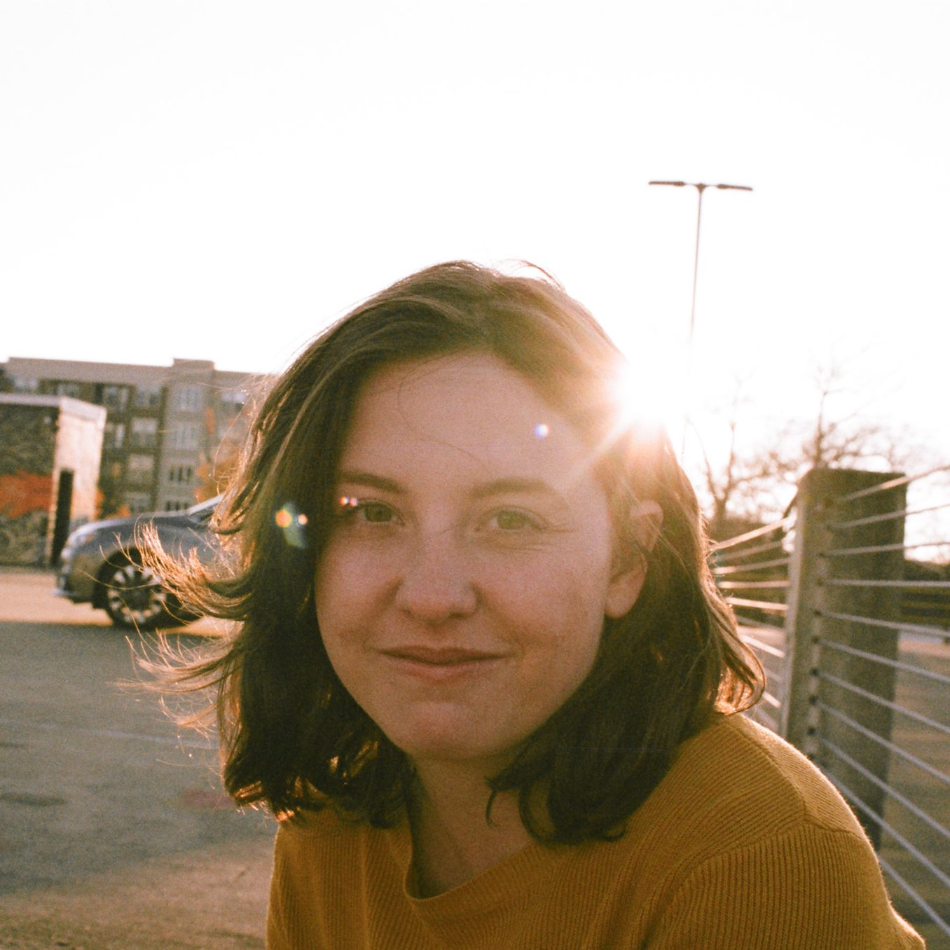Cheyenne Bilderback is sitting on the top floor of a parking garage, with a mural and sunset in the background. She is in her early 20s with wavy brown hair above her shoulders. She is smiling at the camera.