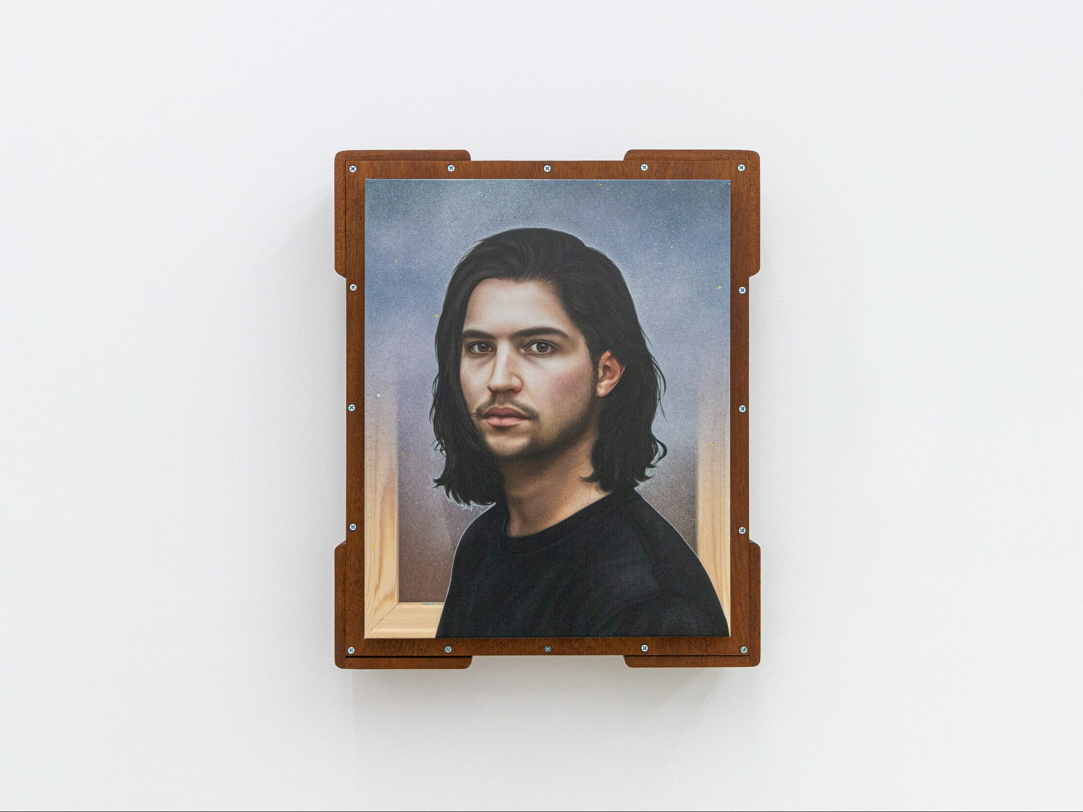 A self portrait hanging on a white wall of a person with medium-length, wavy brown hair, a 5-o'clock shadow and a black shirt stand upright and look through the canvas at the viewer.
