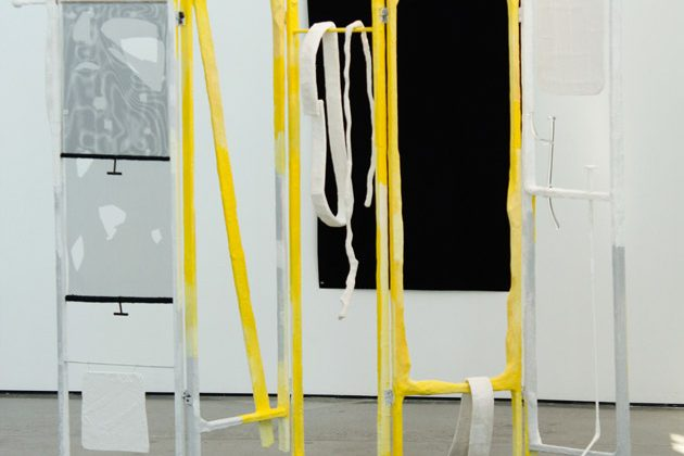 A skeleton of a changing screen is arranged in the center of a gallery space, some of the bones yellow, others white. Scraps of what could be linen are draped over the bars.