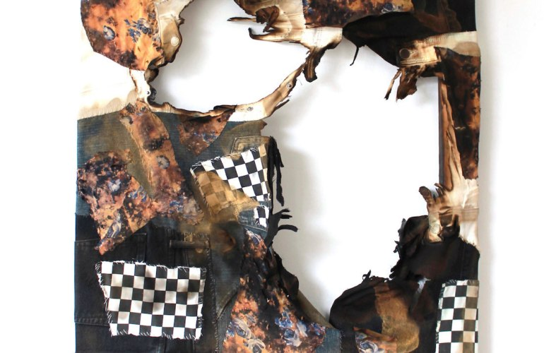A tapestry of fabric, patched together, includes the belt loop from denim pants, black and white checkered fabric—is torn, or maybe burned, with gaping holes in the center.