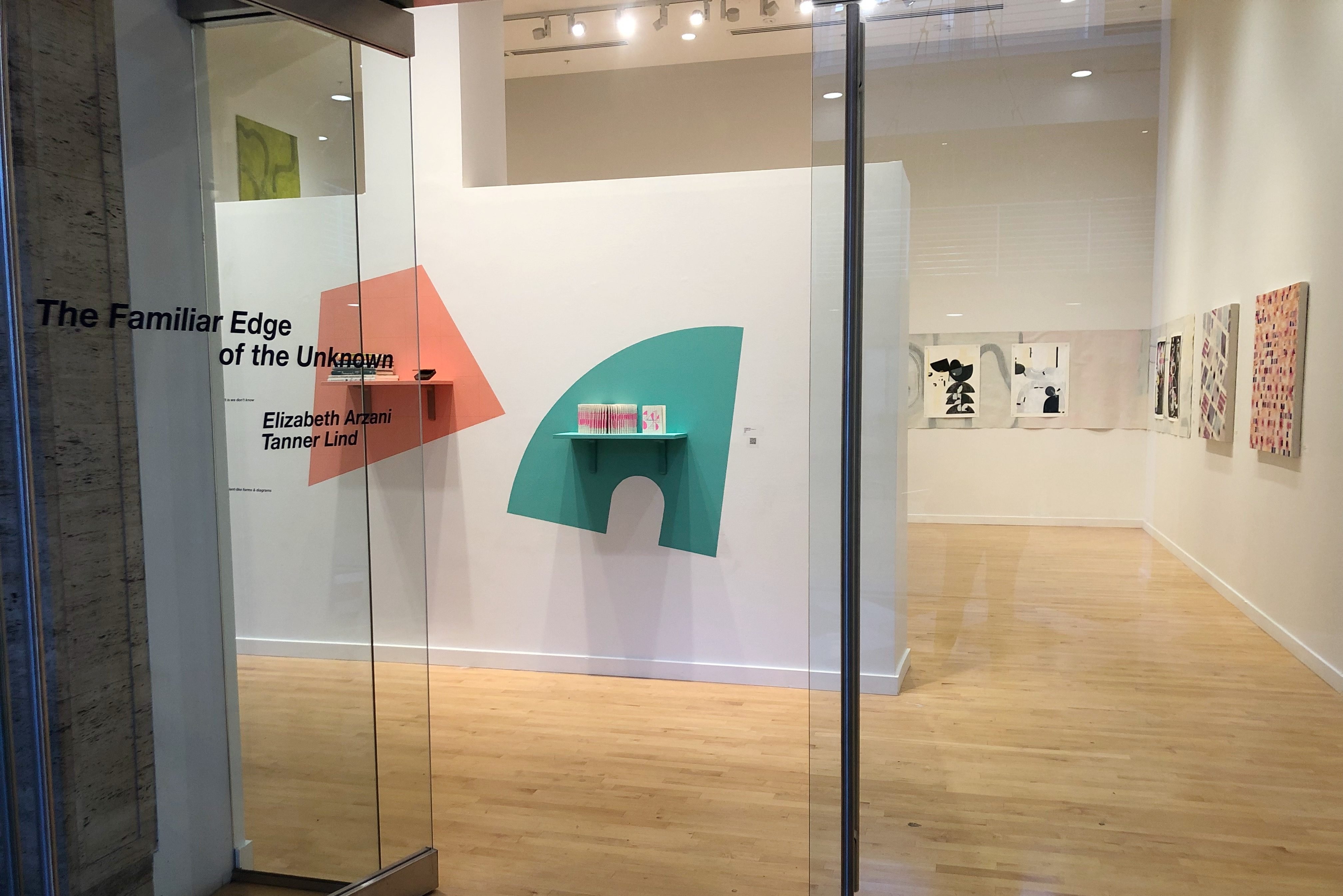 """A glass door, on which are written the words """"The Familiar Edge of the Unknown, Elizabeth Arzani, Tanner Lind,"""" opens into a gallery space with tall ceilings and light wood floors. Beyond the door, various pieces hang on a white wall; and in the middle of the room, shelves hang against soft pastel shapes."""