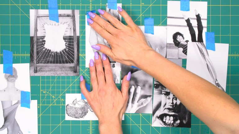 A still from a video, in which a hand presses a photo onto a green grid using blue painters tape, beside other black and white photos of similar sizes.