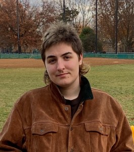 Lucy Talbot Allen standing in front of a baseball field in Autumn. They are a white butch with a short brown mullet. They're wearing a brown suede jacket and smiling slightly at the camera.