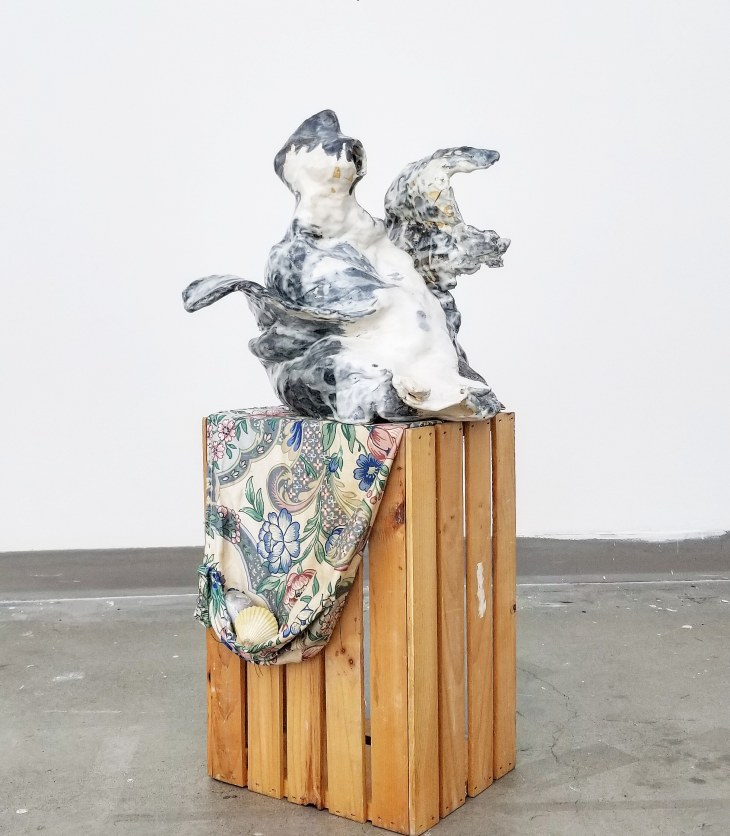 A globby, sculpted figure sits atop a wooden box and the fabric draped over part of it. Painted white and teal-blue, what could be wings or fins or flippers wave playfully.