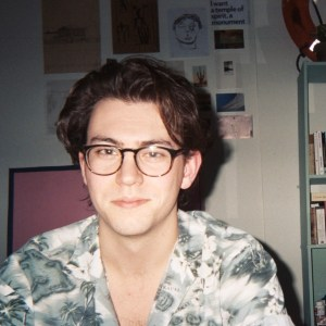 Ethan Beberness sitting in a bedroom in Brooklyn. He is a man in his mid-twenties with light skin tone, a mid-length wavy brown hair and a pair of tortoiseshell glasses. He is smiling at the camera.