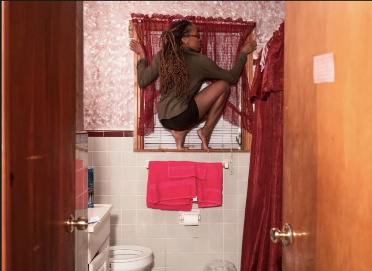 A woman balances, crouched, on the edge of the windowsill above a towel-rode in a small bathroom. The frame of the photograph also includes a red shower curtain, mint wall tiles and floral wall paper.