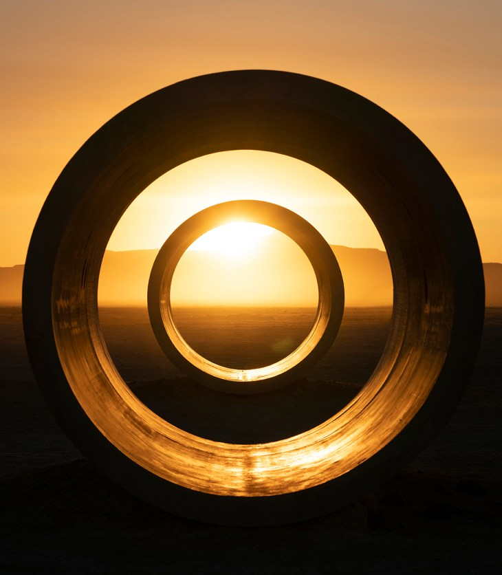 Image of two concentric, dark circles in the middle of a vast landscape with a mountain range at the horizon and the sunrise shining over the top of the mountain through the middle of the circles.