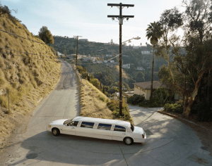 A white limousine snakes around a 90 degree corner, carved into the side of a steep grass hill. In the distance, telephone wire stretches into the jungle of suburbia.