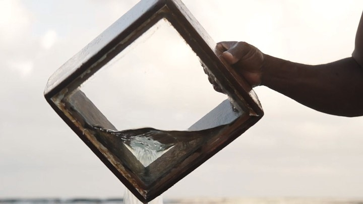 A hand holds a box with a glass bottom in frame, out of which water is pouring. The sky beyond is hazy and grey.