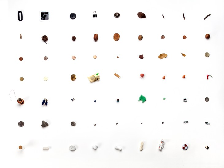 63 small objects are arranged in a grid against a white background, all of them about the size of a quarter, e.g. a cigarette butt, a bottle cap, a spool of string, etc.