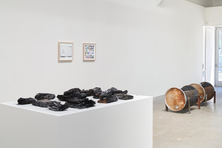 On a white pedestal, piles of charred paper are arranged in a group. Nearby, empty and rusted oil barrels rest on their side. On the wall, two hanged pieces of art hang.