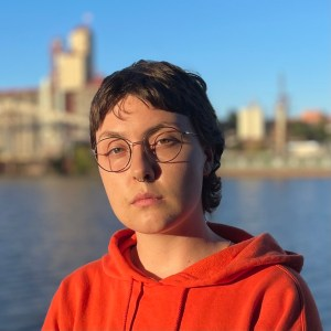 Eel stands with their back facing an industrial portion of the Willamette RIver. They have short hair, round glasses, and are wearing a bright orange hoodie. The setting sun casts a strong light against Eel's face. They have a stern look on their face.