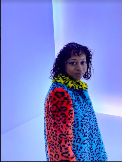 A person with medium-length hair in a cheetah-print coat and a yellow collar turns to look into a camera, a neon wall behind them backlighting the image.