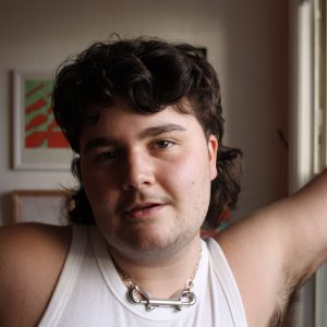 Will Darling, a white trans man, is standing, leaning a hand against a window. He is wearing a white tank top and silver jewelry. He has a slight smile on his face and is looking directly into the camera.