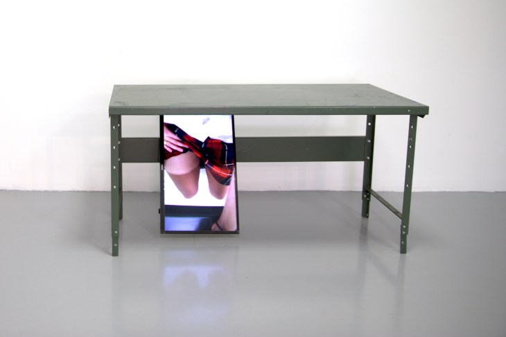 Photograph of a green metal desk underneath which a monitor is playing a video of a hand raising and lowering the hem of a skirt up and down a leg.