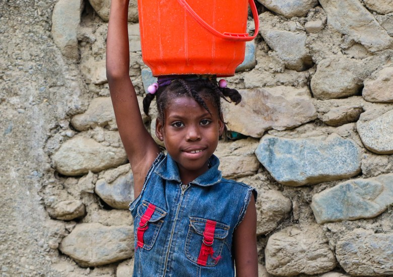 A young girl, carrying a bucket of water on her head in Haut Limbe, Haiti.