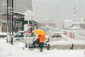 Yokohama, Japan - February 8, 2014: Japanese man gets on a taxi near a train station during snow storm in Yokohama, Japan
