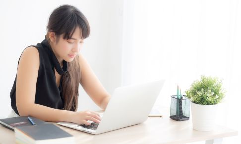 Beautiful young freelance asian woman smiling working and typing on laptop computer at desk office with professional, girl using notebook checking email or social network, business and lifestyle concept.