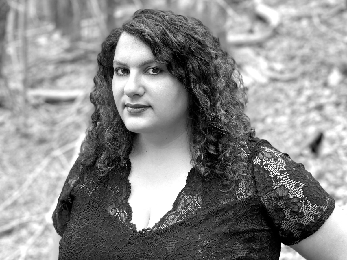 The author Talia Lavin standing in the woods wearing a black top