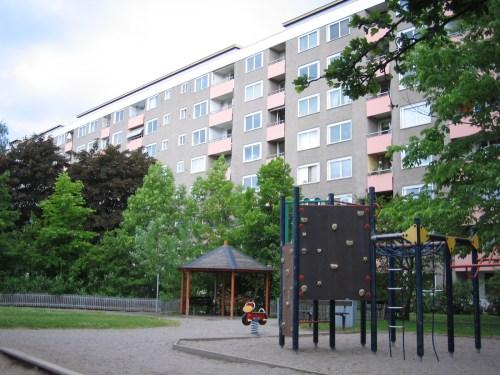 Sommarbild av bostadshus och parklek på Henriksdalsringen